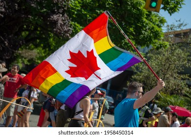 VANCOUVER, CANADA - AUGUST 4: Man holding a canadian rainbow flag at Vancouver Gay Pride parade 2019, on August 4, 2019 in British Columbia, Canada