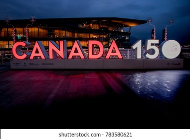 """Vancouver, Canada - December, 2017: """"CANADA 150"""" anniversary celebration sign with illuminated place near Canada Place in Vancouver, British Columbia"""