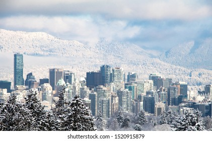 VANCOUVER, CANADA - February 13, 2019: Cityscape view of Vancouver downtown. Tall business building and tower in snow day in winter with mountain view. City of travel destination all year round