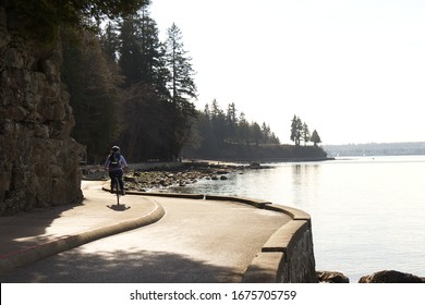 Vancouver, Canada - February 21, 2020: A Woman is riding on the seawall path near The Third Beach in Stanley Park during the Beautiful sunny day