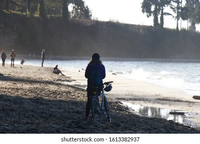 Vancouver, Canada - January 1, 2020: A Woman is standing on the Third Beach in Stanley Park during the Beautiful sunny day
