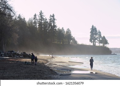 Vancouver, Canada - January 1,2020: A View of Third Beach in Stanley Park in Vancouver during the sunny winter day with people walking in the background