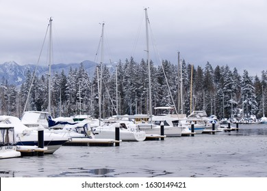 Vancouver, Canada - January 15, 2020: A View of frozen dock with boats in Coal Harbour. Snow storm and extreme weather in Vancouver.