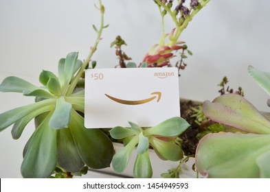 Vancouver, Canada - July 18, 2019:  Amazon Gift Card, succulent background, white and gold $50 gift card for Amazon.com website