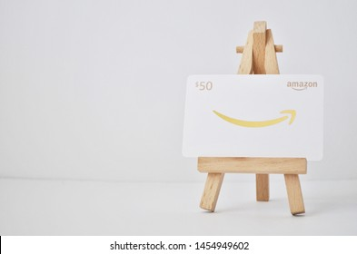 Vancouver, Canada - July 18, 2019:  Amazon Gift Card on a wooden easel and white background, white and gold $50 gift card for Amazon.com website
