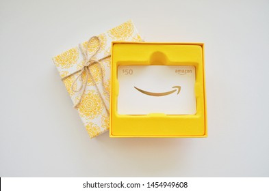 Vancouver, Canada - July 18, 2019:  Amazon Gift Card in a yellow gift box and bow, white and gold $50 gift card for Amazon.com website