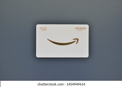 Vancouver, Canada - July 18, 2019:  Amazon Gift Card on light blue background, white and gold $50 gift card for Amazon.com website