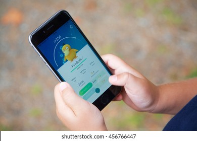 VANCOUVER, CANADA - JULY 22, 2016: A young boy outside playing Pokemon Go on a smart phone.