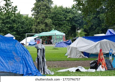 """Vancouver, Canada - July 4, 2020: View of Strathcona Park in downtown Vancouver full of tents and homeless people with sign """"Permanent solutions now"""" in the background"""
