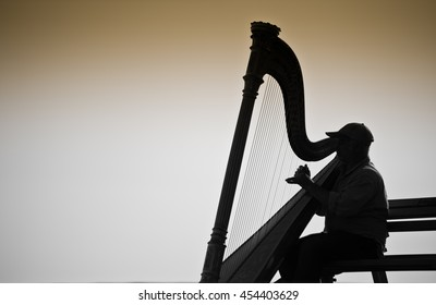 Vancouver, Canada - June 26,2009 : Musician harpist performer silhouette sit on a bench near the sea in Vancouver, Canada
