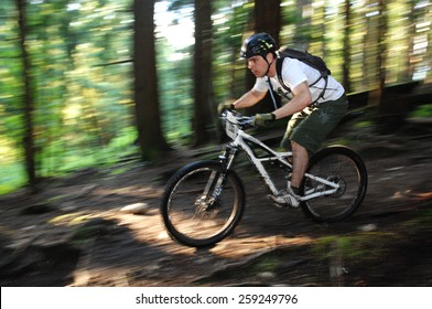 VANCOUVER, CANADA - JUNE 8, 2012: An athlete competes in Adidas Eyeware Chainless Downhill Bicycle Race in the North Shore mountains in North Vancouver, Canada on June 8, 2012.