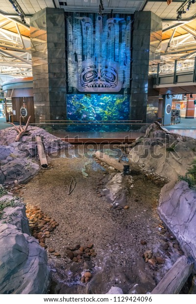 VANCOUVER, CANADA - June 8, 2018: Pacific Northwest Native Indian totem design, aquarium and artificial rock lake in the airport in Vancouver.