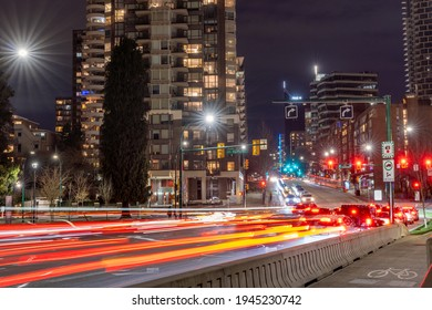 Vancouver, Canada - MAR 11 2021 : Downtown Vancouver cityscape at night. Traffic scene at Burrard Street Bridge and Pacific St crossing.