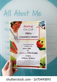 Vancouver, Canada - March 11, 2020: A Woman is holding a colorful menu for ordering food for children at BC Children's Hospital in Vancouver