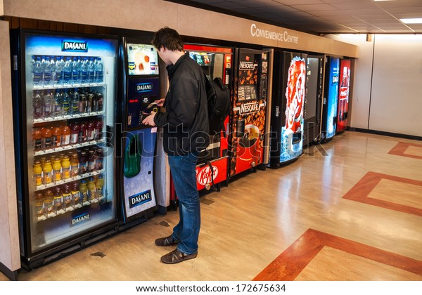 VANCOUVER, CANADA - MAY 12, 2007: Unidentified male student paying for the drinks from the vending machine at Simon Fraser University Convenience Centre.