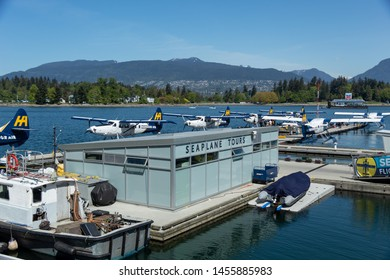 VANCOUVER, CANADA - May 8, 2019: Harbour Air seaplanes docked at Vancouver Harbour Flight Centre in-front of the Seaplane Tours building.
