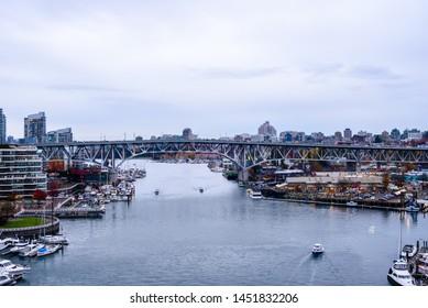 VANCOUVER, CANADA - OCTOBER 27, 2018: The Granville Bridge passes over False Creek and the Granville Island public market.