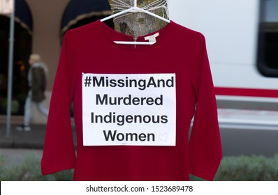"Vancouver, Canada - October 5, 2019: A red dress with text ""Missing And Murdered Indigenous Women"" is hanging on the tree. Art Memorial to honour Missing and Murdered Indigenous Women in US and Canada"