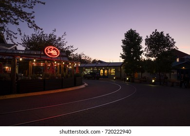 VANCOUVER, CANADA - SEPTEMBER 13, 2016: restaurants and shops line a quiet street in Granville Island at dusk.