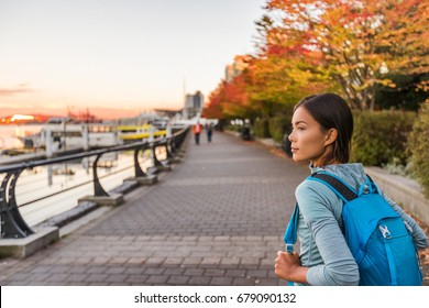 Vancouver city urban lifestyle people at Harbour, British Columbia. Woman tourist with student backpack in city outdoors enjoying autumn season.