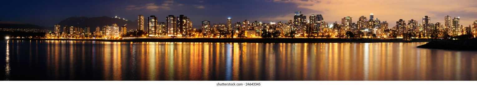 The Vancouver downtown at night glittering against a backdrop of dark mountains.