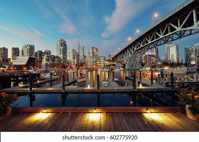 Vancouver False Creek at night with bridge and boat.