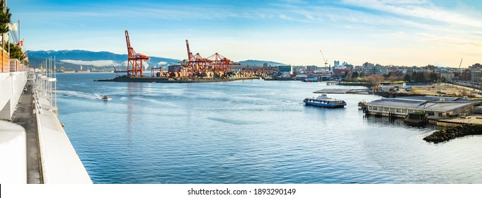 Vancouver Harbour panorama early mornings, on a sunny day. Waterfront city skyline with industry. A seabus ferry is leaving the waterfront station. Industrial cranes with cargo containers and tanker.  - Shutterstock ID 1893290149