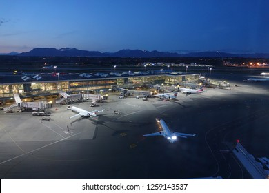 VANCOUVER INTERNATIONAL AIRPORT, CANADA, MARCH 2018: AERIAL: Cool shot from above of commercial aircrafts being serviced by the illuminated terminal on busy morning at Vancouver International Airport.