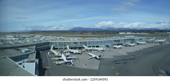 VANCOUVER INTERNATIONAL AIRPORT, CANADA, MARCH 2018: AERIAL: Large white Delta and Air Canada airplanes getting ready for boarding at Vancouver International Airport. Aircrafts surrounding airport.