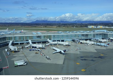 VANCOUVER INTERNATIONAL AIRPORT, CANADA, MARCH 2018: DRONE: Big commercial airplanes connected to Vancouver International Airport terminal getting ready for departure. Delta and Air Canada aircrafts.