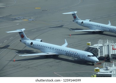 VANCOUVER INTERNATIONAL AIRPORT, CANADA, MARCH 2018: DRONE: Air Canada Express commercial airplane is connected to a walkway coming out of the airport. Plane getting ready for boarding procedure.