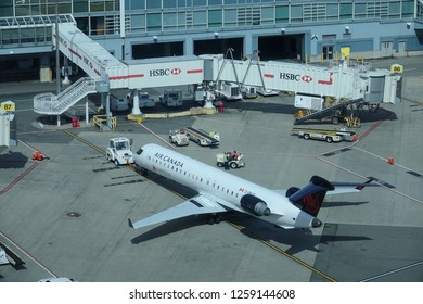 VANCOUVER INTERNATIONAL AIRPORT, CANADA, MARCH 2018: AERIAL: Air Canada passenger aircraft getting serviced before taking off from sunny Vancouver. Airport service vehicles buzzing around the plane.
