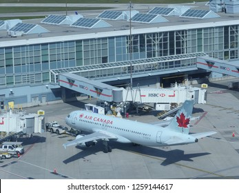 VANCOUVER INTERNATIONAL AIRPORT, CANADA, MARCH 2018: CLOSE UP: Large Air Canada passenger plane is serviced by terminal before boarding. Vancouver International crew preparing airplane for take off.