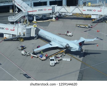 VANCOUVER INTERNATIONAL AIRPORT, CANADA, MARCH 2018: CLOSE UP: Air Canada Express airplane is connected to the airport walkway while being serviced by the airport staff before boarding procedure.