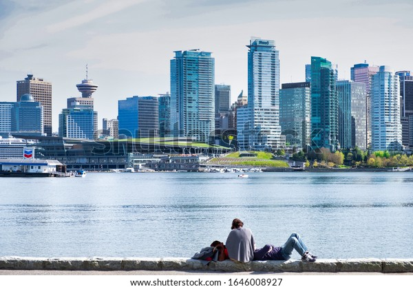 VANCOUVER - MAY 05 2019: Downtown Vancouver, Canada.View of Downtown Vancouver,from Stanley park, two people are lying on the quay
