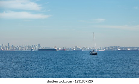 Vancouver skyline with a sailboat and tanker ships on a sunny day.