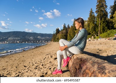 Vancouver urban lifestyle woman relaxing on Third Beach in Stanley Park, Vancouver, BC, Canada. Canadian Asian girl sitting on tree trunk at popular sandy resting area of canadian city.