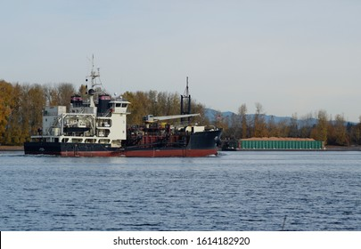 Vancouver, WA USA – Nov. 14, 2019: The US Army Corps of Engineers dredge Yaquina rides high in the water after dumping a load of Columbia River bottom. A bin barges full of sawdust is moored behind.