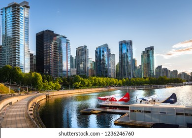 Vancouver Waterfront at Sunset. Two Seaplanes Moored to a Jetty are in Foreground. Vancouver, BC, Canada.
