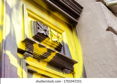 Vandalised, spray painted antique old wooden door detail, destroyed dated architecture, urban vandalism, building sprayed with yellow paint, crime, devastating historical buildings, cultural heritage