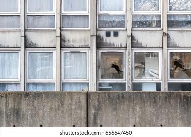 Vandalism, broken windows of a dilapidated council flat housing block, Robin Hood Gardens, in East London