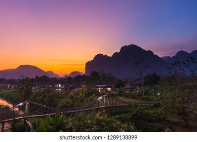 Vang Vieng backpacker travel destination in Laos, Asia. Sunset over scenic cliffs and rock pinnacles, rice paddies valley, stunning landscape.