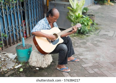 Vang Vieng, Laos - Aug 20 - Unidentified asian people playing guitar on roadside on August 20, 2014.
