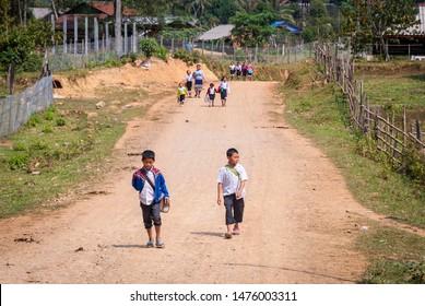 Vang Vieng, Laos - Feb 2016: Kids walking home from school in Laotian countryside