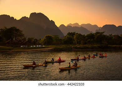 VANG VIENG, LAOS - FEBRUARY 23, 2014: Tourists was canoeing in the Song river in Vang Vieng with sunset view behind the mountain.