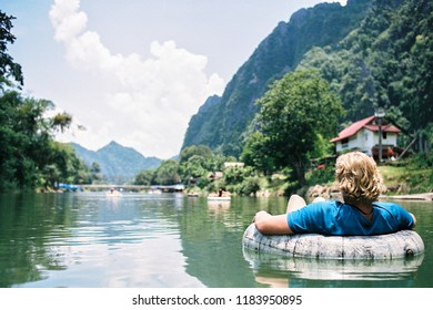 Vang Vieng, Vientiane / Laos - May 16th 2018: A Young Tourist Tubing On The Nam Song River On A Beautiful, Clear Day