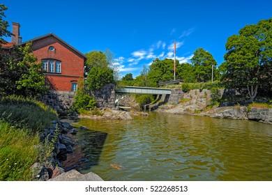 Vanhankaupunginkoski waterfall on Vantaanjoki River and Power Plant Museum buildings located in Old Helsinki on the Western fork of the Vantaa River.