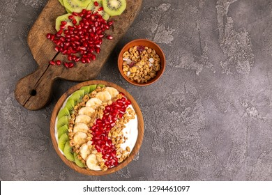Vanilla acai bowl with kiwi, banana, pomegranate and granola with ingredients on vintage cutting board. Dark concrete background. Healthy food concept. Top view