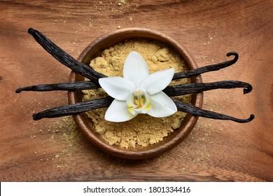 Vanilla beans and vanilla powder in a wooden bowl