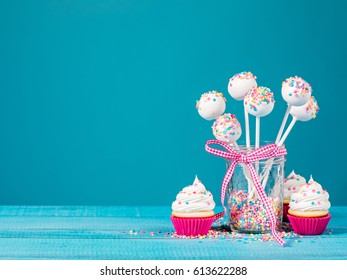 Vanilla cake pops and cupcakes on a blue background.